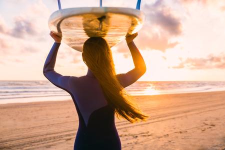 長い髪の女の子をサーフィンはサーフィンに行きます。夕日や日の出でビーチでサーフボードと女性。サーファーと海