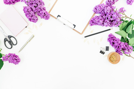 minimal: Freelance of blogger workspace with clipboard, notebook, scissors, lilac and accessories on white background. Flat lay, top view. Beauty blog concept. Stock Photo