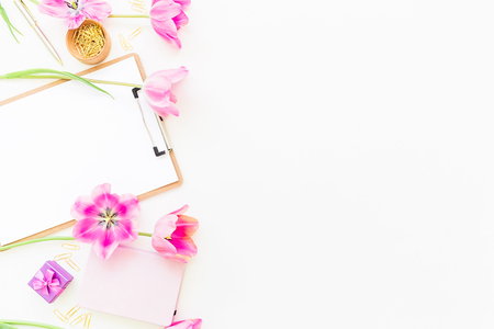 Beauty blog concept. Freelancer or blogger workspace with clipboard, notebook, pink tulips and accessories on white background. Flat lay, top view.
