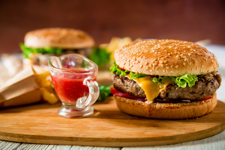 Classic hamburger with beef and tomato sauce on wooden plate. Tasty food concept Stock Photo