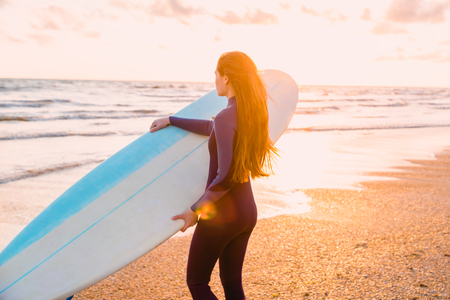 Young beautiful woman with long hair. Surf girl in wetsuit with surfboard on a beach at sunset or sunrise. Stock Photo