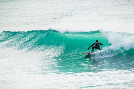 Surfing in turquoise barrel in the ocean