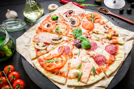 Italian food. Pizza with ingredients, spices, oil and vegetables on a dark background. Flat lay, top view.