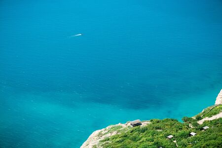 Blue sea and shore with trees. Summer day on ocean Stock Photo