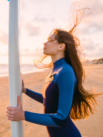 Beautiful surf girl with long hair holding surfboard at sunset.