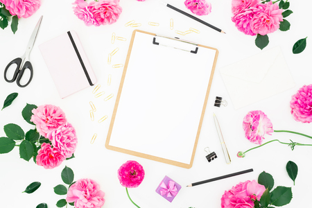 Minimalistic styled workspace with clipboard, notebook, purple roses, ranunculus and accessories on white background. Flat lay, top view. Blogger of freelancer workspace