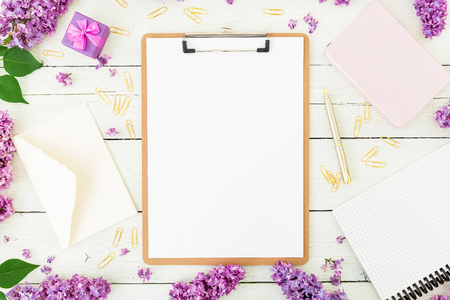 Minimalistic workspace with clipboard, envelope, lilac and accessories on white background. Freelancer or blogger concept. Flat lay, top view.