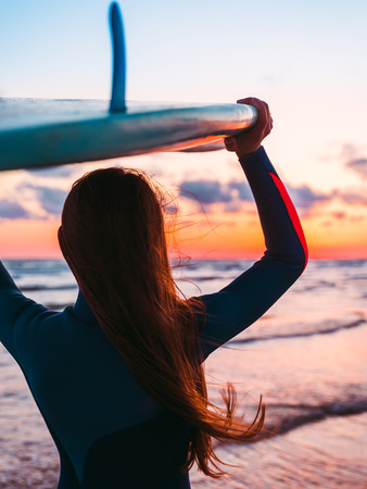 Surf girl with long hair holding surfboard on beach at sunset or sunrise. Surfer and ocean