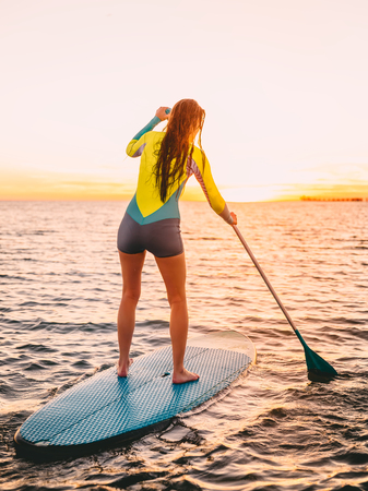 Attractive young woman standing up paddle surfing with beautiful sunset or sunrise colors