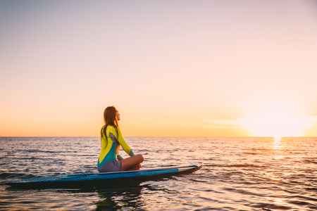 daybreak: Young girl on stand up paddle board on a quiet sea with warm summer sunset colors. Relaxing on ocean
