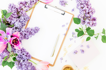 Workspace with clipboard, notebook, pen, purple flowers and accessories on white background. Flat lay, top view. Freelancer or blogger desk