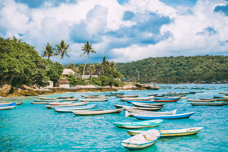 Tropical island in Indonesia, blue ocean and boats. Stock Photo