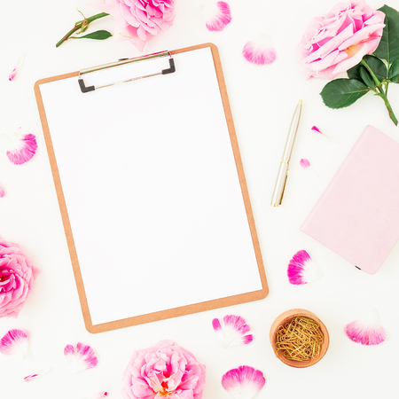 Minimalistic workspace with clipboard, purple roses and accessories on white background. Flat lay, top view. Blogger of freelancer concept