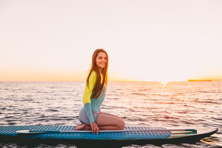Stand up paddle boarding on ocean with warm sunset colors. Young girl relaxing on sea Standard-Bild