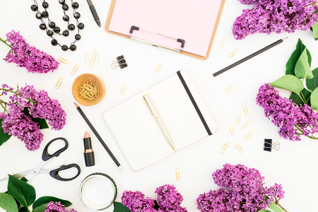 Freelancer or blogger workspace with clipboard, notebook, lipstick, lilac flowers and accessories on white background. Flat lay, top view. Beauty blog composition.