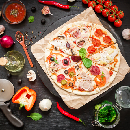 Hot Italian pizza, spices, oil and vegetables on dark background. Flat lay, top view.