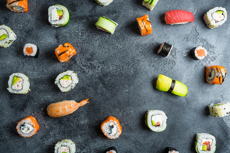 Pattern of sushi rolls on a dark background. Japanese food