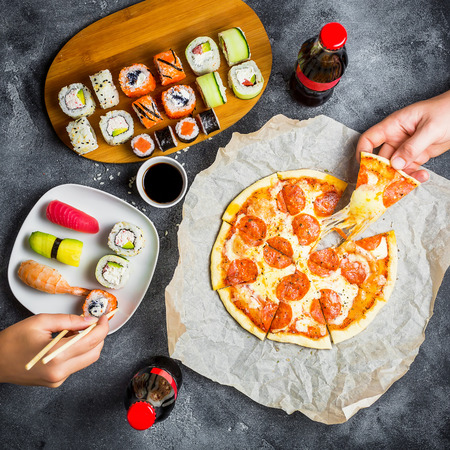 Pizza and sushi rolls and hands take food. Food and soda drinks at table. Food background. Flat lay, top view.