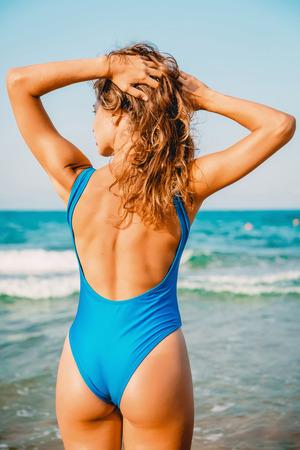 Het portret van de zomer van een vrouw met perfect lichaam en het kijken op zee.