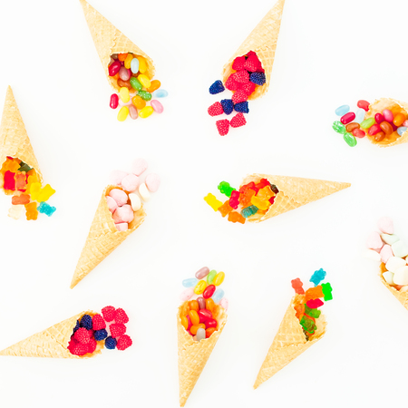 kids birthday party: Waffle cones with colorful bright candy on white background. Flat lay, top view Stock Photo