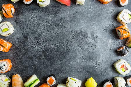 Food frame with set of Japanese food on dark background. Sushi rolls, nigiri, raw salmon steak, rice, and avocado. Flat lay. Top view