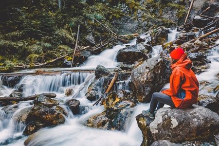 Hiker young girl is sitting on a rock near a mountain river. Beautiful nature in the mountains. Stock Photo