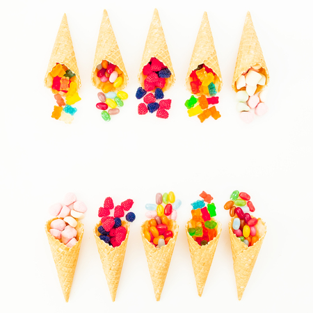 Waffle cones with colorful bright candy on white background. Flat lay, top view Stock Photo