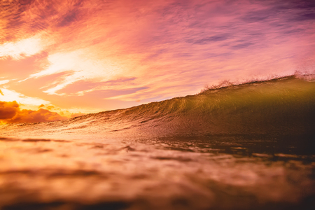 Wave in the ocean at sunset or sunrise. Wave and sun light with cloudy sky Stock Photo