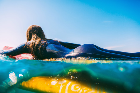 Surf girl on the surfboard. Woman with surfboard in the ocean during surfing. Surfer and ocean Stock Photo - 88211965