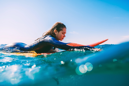 Surfer girl on surfboard. Young woman in the ocean during surfing.