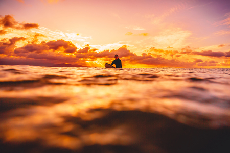 Surfer in the ocean at sunset or sunrise. Winter surfing in ocean Stock Photo - 88655531