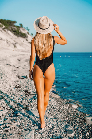 Back view of perfect woman in bikini with bonnet relaxing at sea