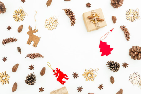 Christmas gift box with decoration and pine cones on white background. Flat lay, top view. New year concept.
