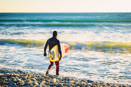 winter sunrise: Surfer with surfboard on the beach at sunset or sunrise. Surfer and ocean waves