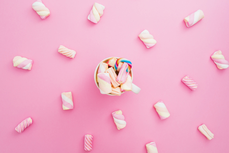 Marshmallow and cappuccino mug with sugar cane on pink background. Candy concept. Flat lay, top view. Stock Photo