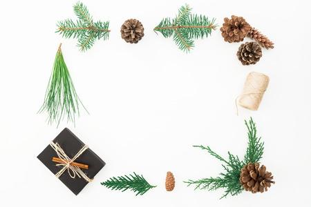 Kerstmiskader van giftdoos, takken van boom en denneappels op witte achtergrond wordt gemaakt die. Plat leggen. Bovenaanzicht