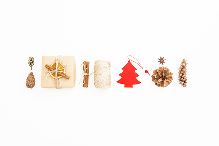 Holiday composition. Gift box, Christmas decoration, cinnamon and pine cones on white. Flat lay, top view