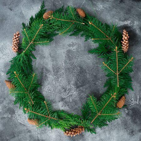 Kruhový rám z vánočního stromku a borovice kužele na tmavém pozadí. Zimní, složení nového roku. Ploché leželo. Pohled shora