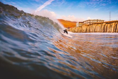 Surfer on surfboard ride at barrel wave. Winter surfing