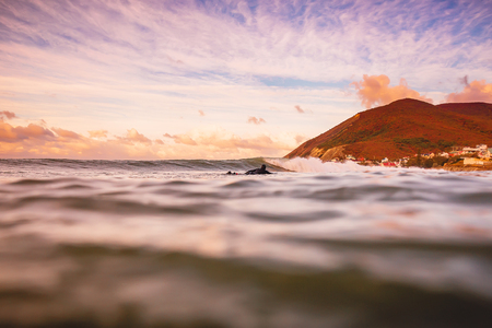 Wave in the ocean at bright sunset or sunrise with surfer.