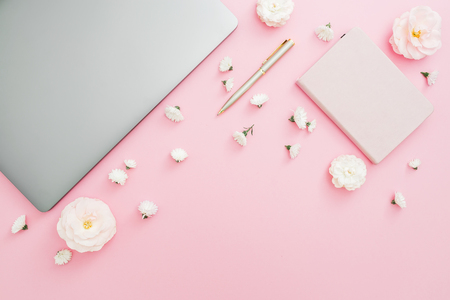 Stylish office desk workspace with laptop, notebook, pen and flowers on pink background. Top view. Flat lay lifestyle concept.