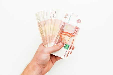 Russian banknote 5000 rubles in men hand on white background