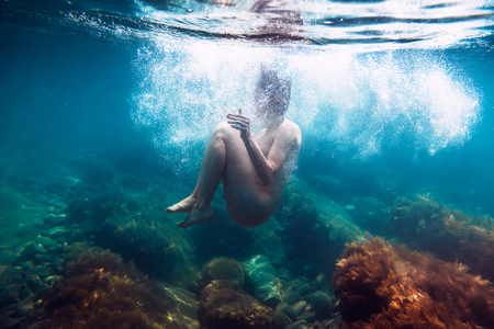 Naked woman with bubbles is underwater swimming in the ocean Foto de archivo