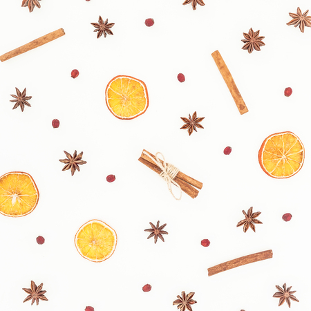 Christmas or New Year concept. Pattern of cinnamon, anise and dried citrus on white background. Flat lay, top view.