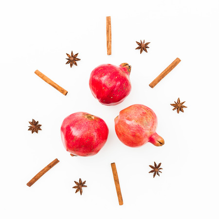 Garnet fruits, cinnamon and anise on white background. New year concept. Flat lay. Top view