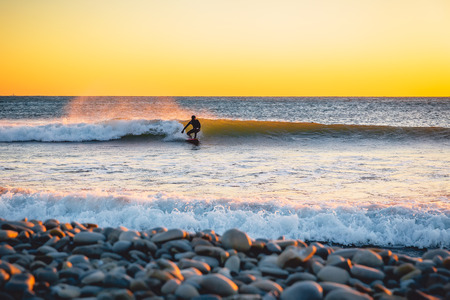 Surfer at sunset or sunrise. Winter cold surfing in wetsuit
