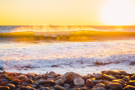 Crystal ocean wave at colorful sunset or sunrise. Stock Photo