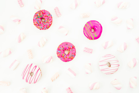 Delicious pink donuts with marshmallow on white background. Flat lay, top view Stock Photo