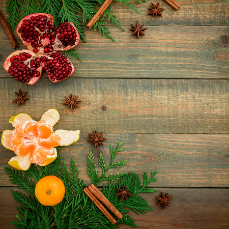 New year concept. Fresh delicious garnet, citrus, cinnamon and anise on a wooden background. Flat lay. Top view. Christmas concept