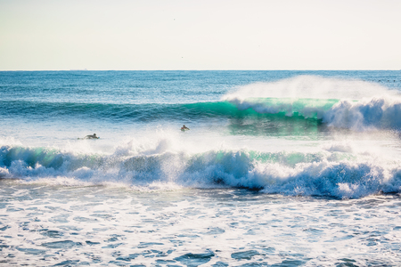 Perfect breaking blue wave and surfers